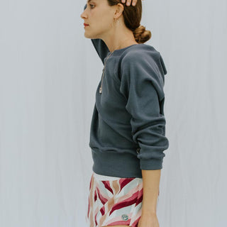 side view of model wearing long sleeve raglan sweater and striped lounge shorts