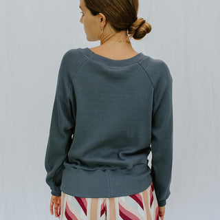 back view of model wearing long sleeve raglan sweater in blue with striped vintage lounge shorts