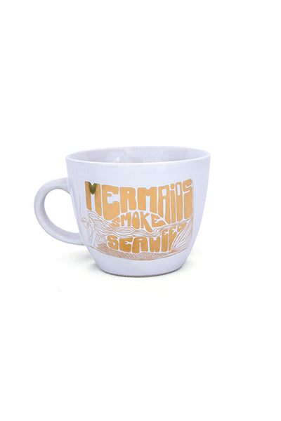 white ceramic mug with gold decal on the front mermaids smoke seaweed wings hawaii
