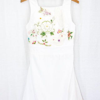 white pinafore dress, sleeveless and with vintage floral needlework stitched on the bust