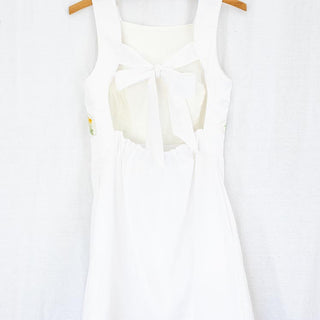 white sleeveless dress with open back and tie