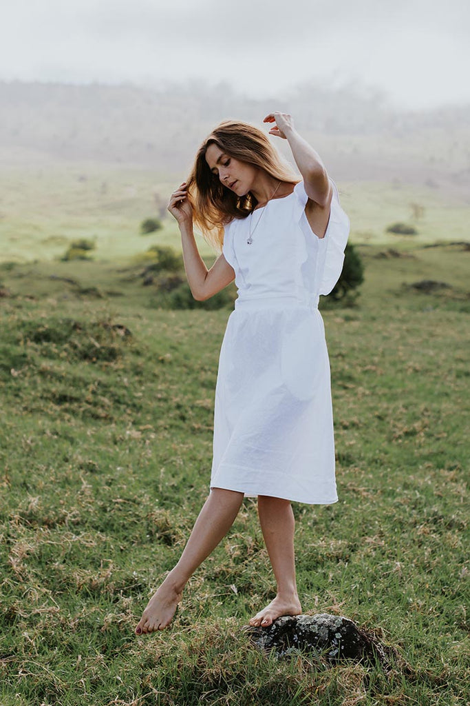 model wearing white dress with flutter sleeves . standing in a field