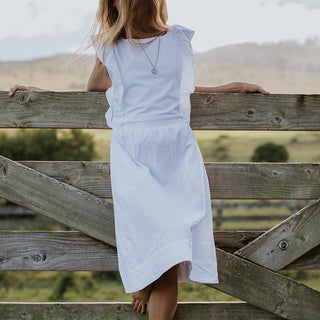 model wearing white pinafore dress standing on a wood fence in a field
