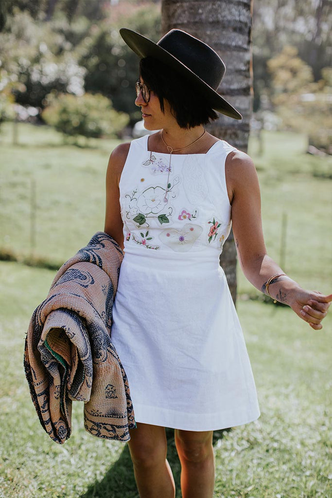 model wearing white pinafore dress with a hat, holding a kantha blanket