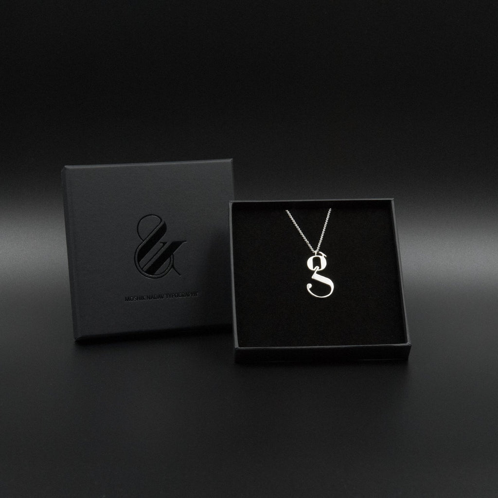 Silver Lowercase g necklace Designed by Moshik Nadav Typography with Paris Pro Typeface