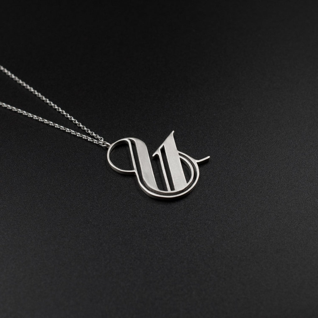Beautiful silver ampersand necklace by Moshik Nadav Typography