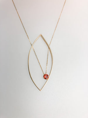 Petal-like pendant necklace with an offset Red Tourmaline stone gracefully hangs on a delicate gold chain