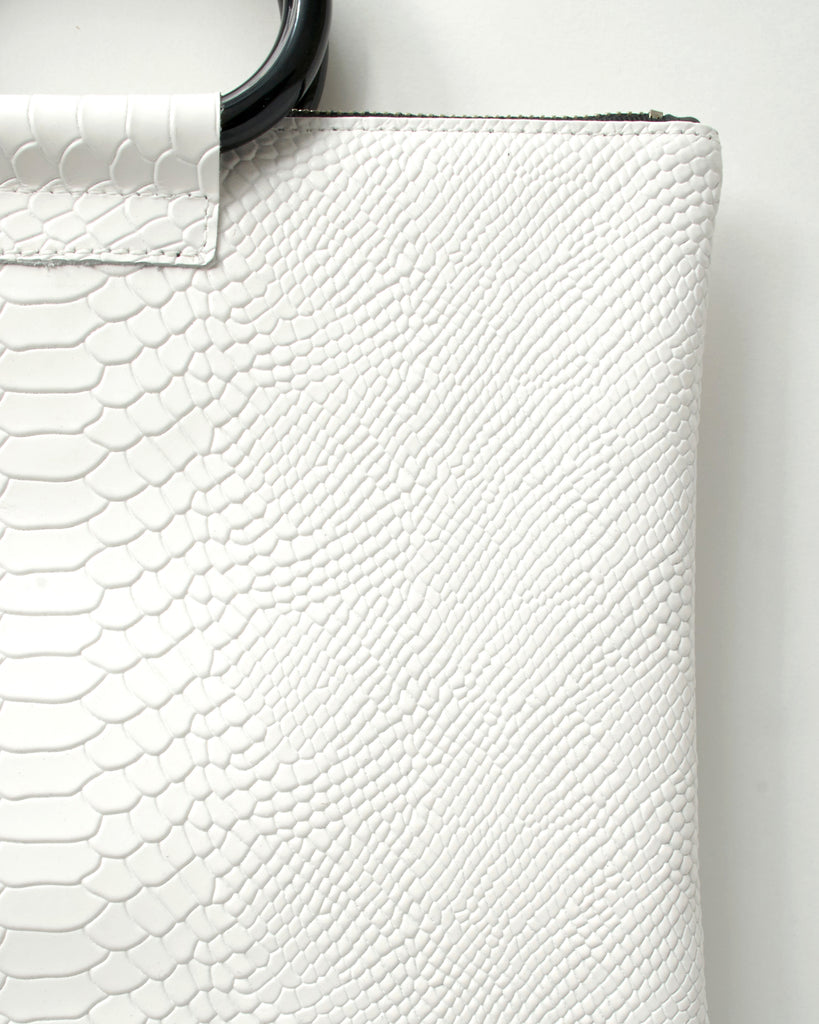 jolie clutch with black handles in white snake leather