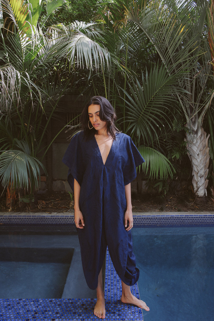Pull over indigo embroidered kaftan with deep-v neckline and side opening at waist.