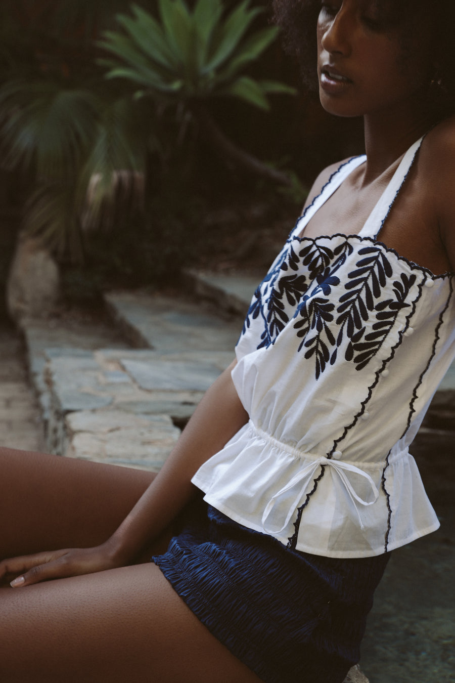 Lightweight 100% pima cotton camisole in white with indigo blue embroidered petals, delicate side covered buttons, and an adjustable drawstring waist.