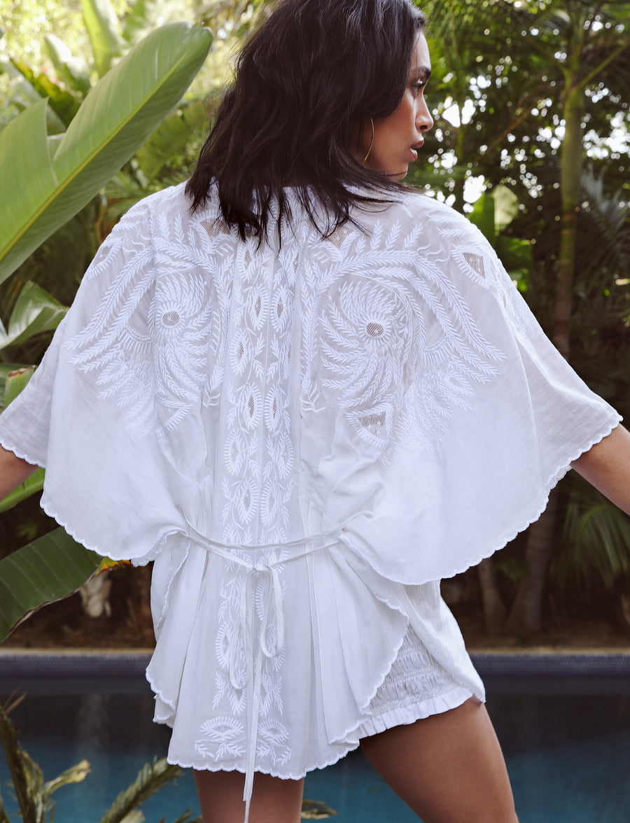White embroidered cape/cover-up lays over shoulders with ties at neck and waist.  Darted back creates defining back peplum with a vintage flair.