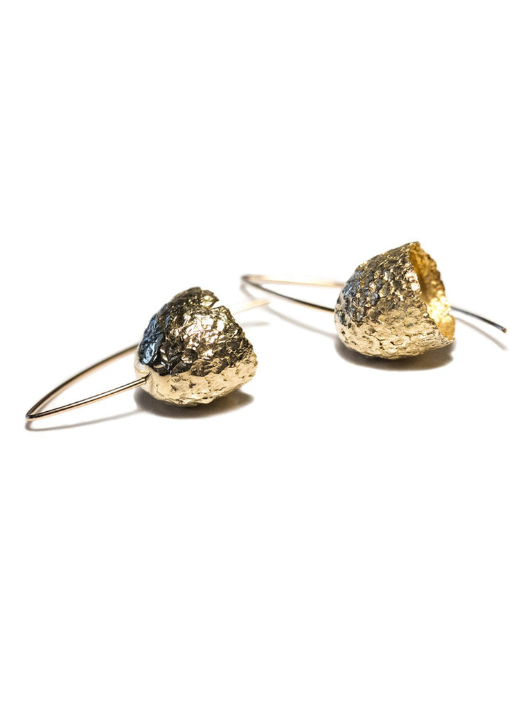 These light dangle earrings were inspired by the top of an acorn, the cupule. The scaly textured caps hang and swing beautifully from the minimal ear wires, reminiscent of little bells. Kirsten Meunster's work distills and reinterpret nature's diverse patterns, textures, forms and imperfections.