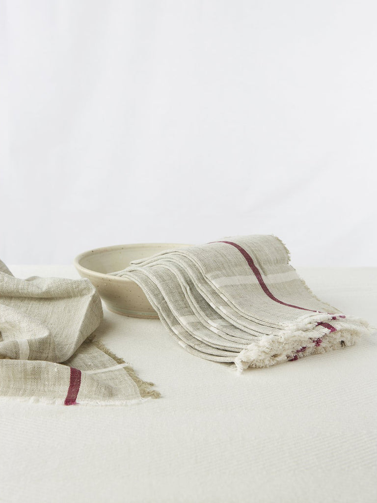 "Pale gray napkins with a deep burgundy stripe. Made from 100% cotton khadi. Khadi is a fabric woven by hand of hand-spun yarn. Set of 6. Napkins measure 18″ X 18""."