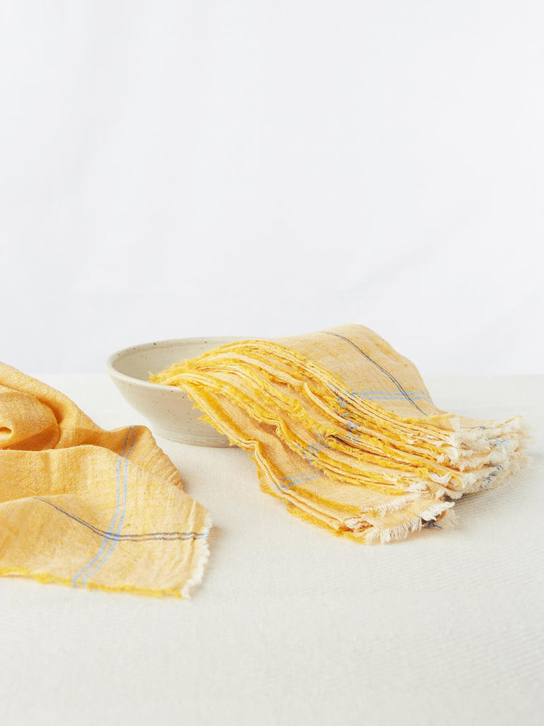 "Cheery Yellow napkin sets made from 100% cotton khadi. Khadi is a fabric woven by hand of hand-spun yarn. Set of 6. Napkins measure 18″ X 18""."