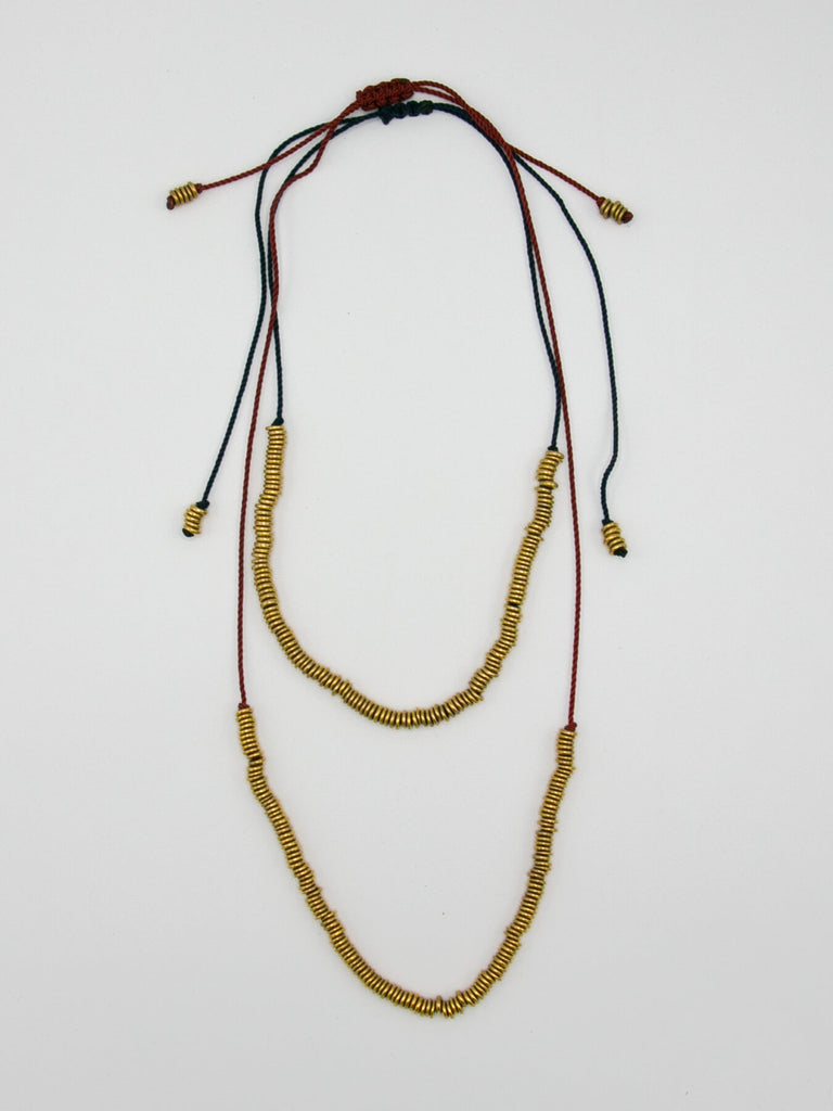 "A row of shiny lacquered brass beads on repurposed neon mason twine. Decorative pull tabs allow for adjustable length from 11""-34"". Pull the tabs to lengthen and shorten. Can be worn as a choker, long necklace or anywhere in between. Wear the long tabs in front or hidden down the back. The row of beads is 9"" long. Handmade in Brooklyn, NY."