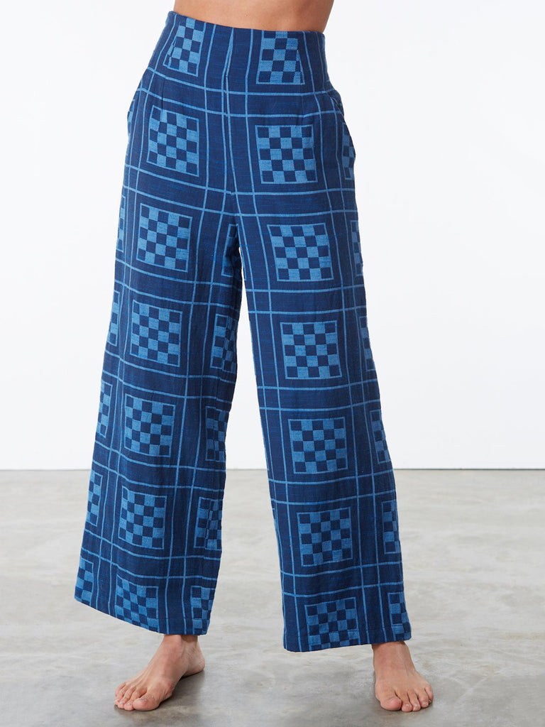 A comfortable, cropped pant with a pleated front and an elasticated back waistband. Light and airy. Features side slit pockets. 100% handwoven cotton. Made in India.