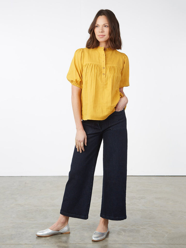 High-waist, wide leg jeans cut from stretchy Indigo denim. Features 1970's inspired front and back pockets, hidden button fly and wed cropped length.