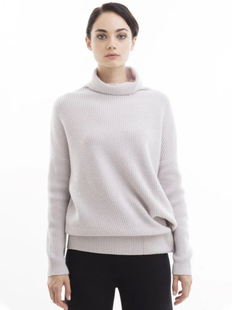 A staple of our fall/winter offering, this Turtleneck Pullover has a chunky, cozy appearance. Made from a soft, yet lightweight, air-spun wool cashmere blend, this sweater has an unexpected lightweight, soft warmth. Oversized fit with fitted sleeves. Snap panel at the bottom allows wearer to wear loose or fitted at the waist.