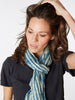 "A lightweight scarf made from 100% whisper-thin cotton voile. Hand block printed indigo stripes. Measures 19″ X 80""."