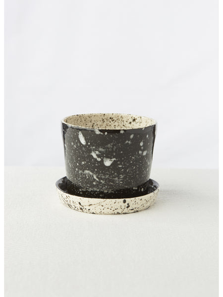 "Porcelain planter thrown on the wheel with hand painted black and white speckled details. Features an attached saucer with 3 drainage holes. Measures approximately 4"" x 3.5"". Because every item is made by hand, variation in size and shape are to be expected and embraced."