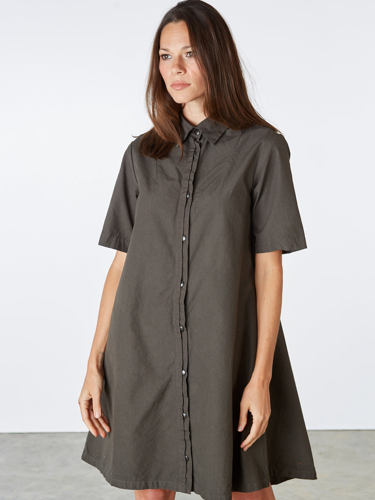 Shirt dress with A-line shape. Features hidden pockets at the hips and a hidden front snap placket. Flared short sleeves. 100% cotton. Machine wash cold. Made in Seattle, WA.