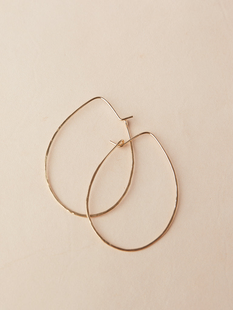Delicate, featherweight hoops in a unique egg shape. 14K gold fill. Hand shaped with hammered texture.