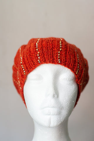 Knitted beanie in burnt orange with gold seed beads