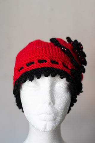 Knitted red cloche hat with seed beads and rosette