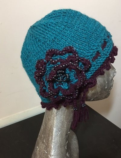 Knitted Pacific blue cloche hat with seed beads and rosette