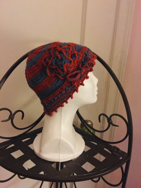 Knitted orange and blue-gray striped cloche hat with rosette