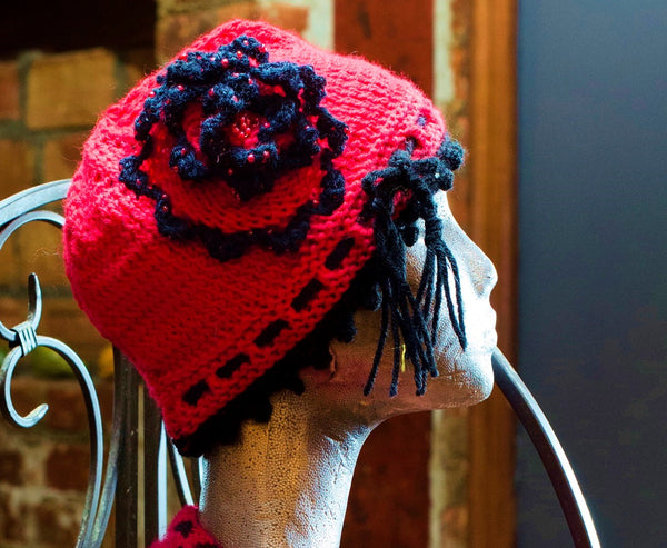 Knitted pink striped cloche hat with seed beads and rosette