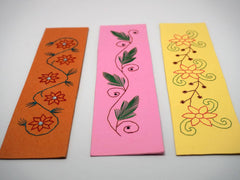 Three embroidered bookmarks with flowers