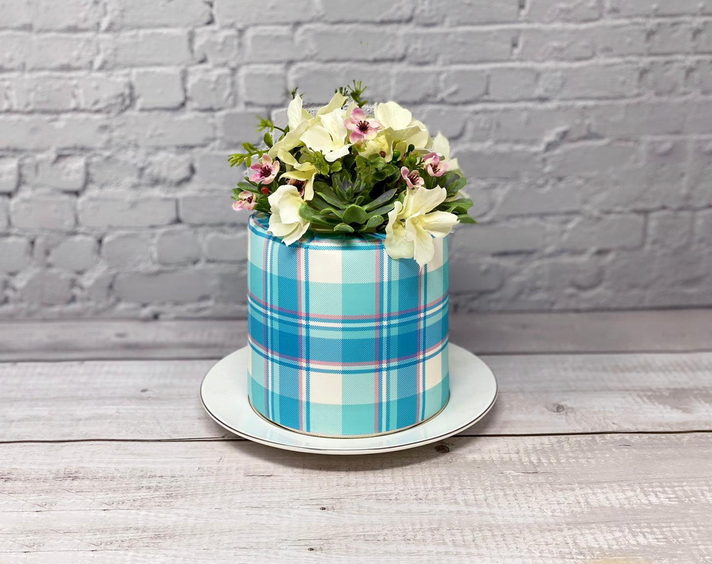 Aqua and pink icing cake wrap with a floral arrangement on top
