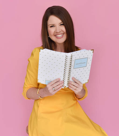 Team member holding daily and weekly versions of Simplified Planner