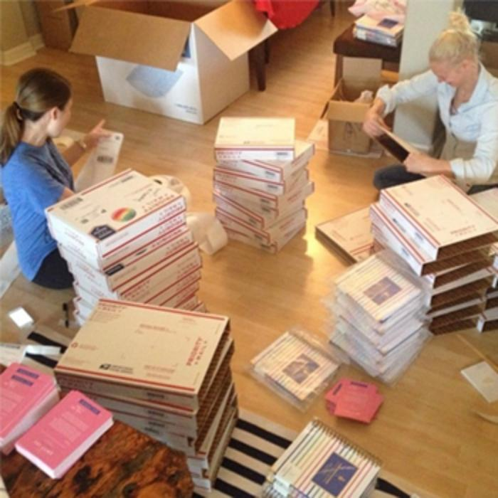 friends sitting on the floor, packing boxes