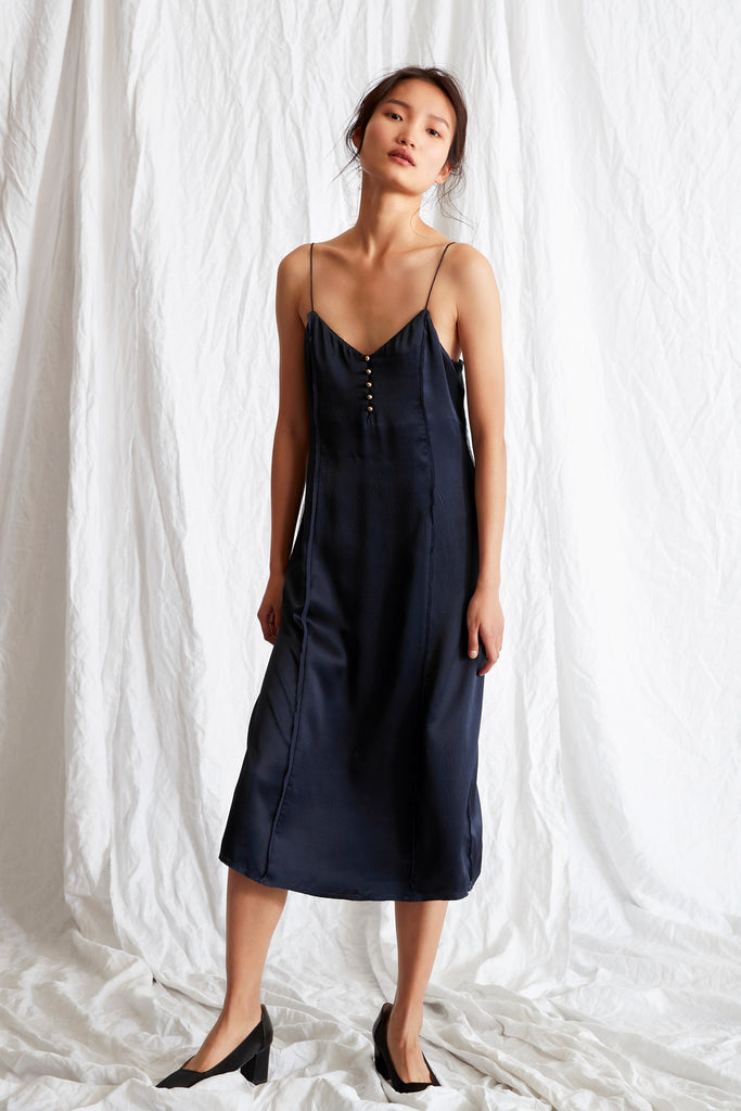The Piedra Slip Dress is a relaxed, midi length style with fine straps and gold button detailing in the front. This style is crafted in a textured silk fabrication.