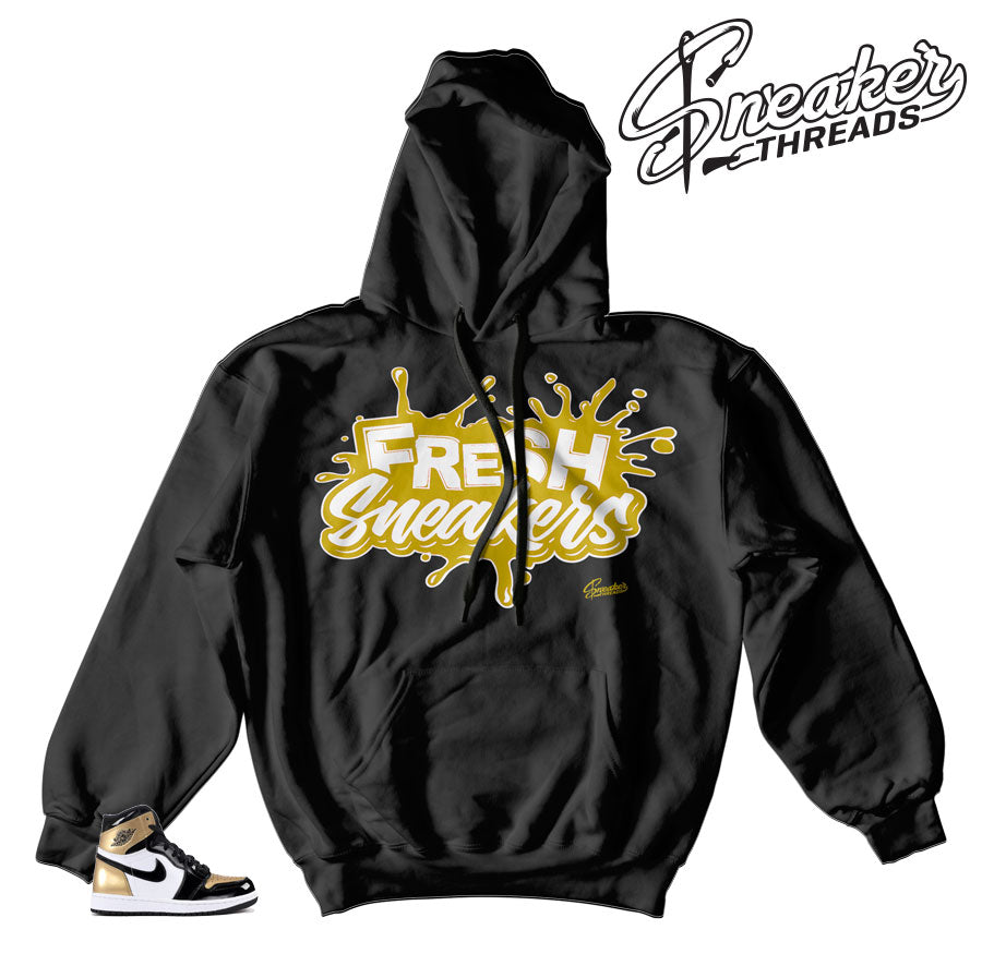 Sweatshirts match Jordan 1 NRG gold toe sneakers.