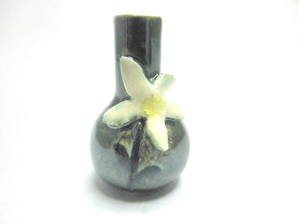 Miniature ceramic vase with white flower on black