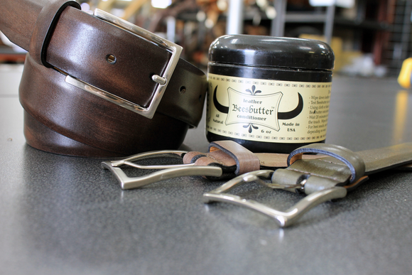 brown remo tulliani jackson belt coiled next to leather butter container with two belts