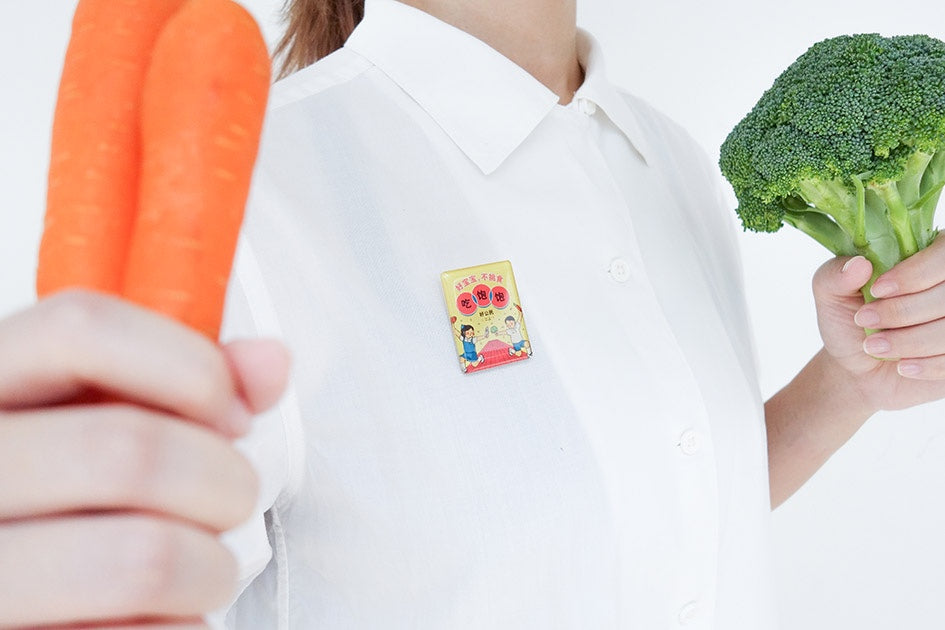 photograph of a person holding a carrot and broccoli while wearing a white button up shirt with a chinese acrylic pin
