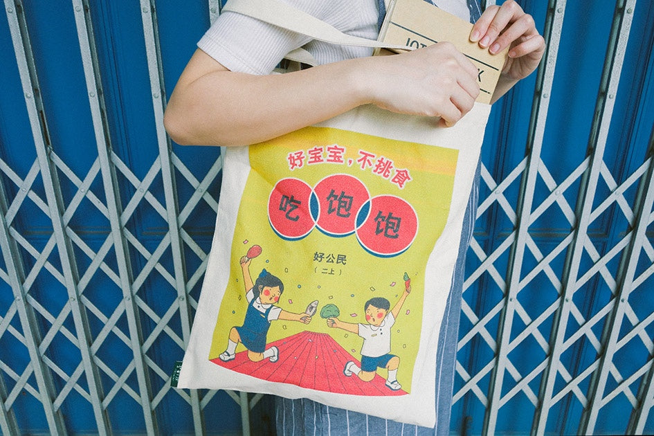 photograph of a person carrying a totebag with a chinese design about not being picky while walking