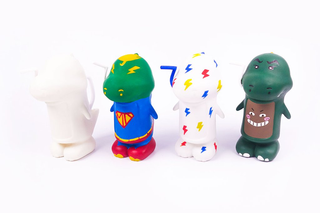 image of 4 milo dinosaur vinyl toys painted differently with paints standing in a row facing the left