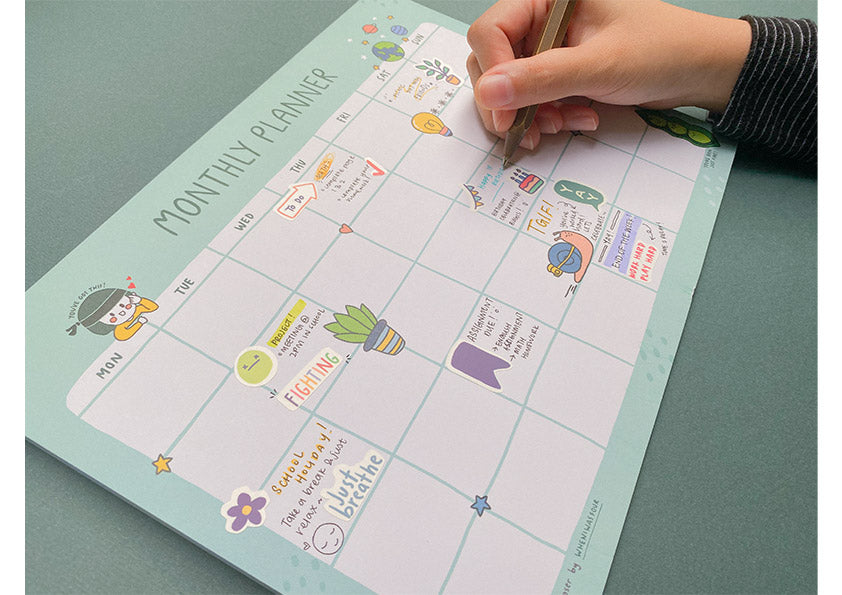 photograph of someone writing in a monthly calendar decorated with colourful stickers to keep track of events and tasks