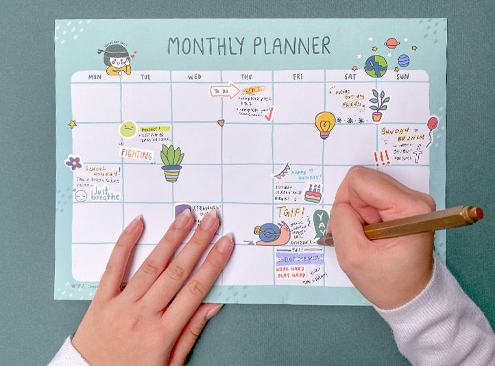 photograph of someone writing her plans and decorating the monthly planner with colourful stickers to keep track of tasks and events