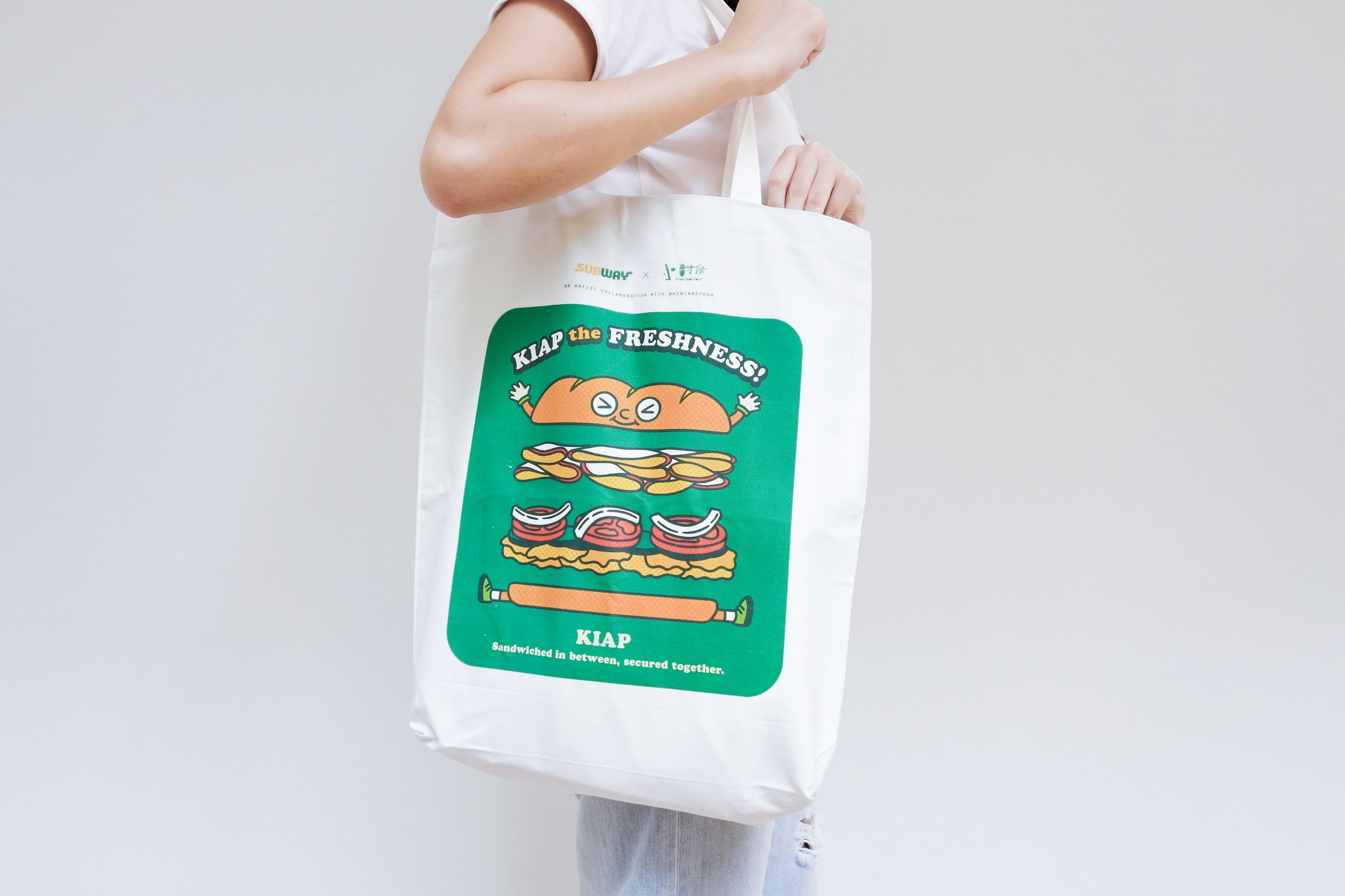 image of a person carrying a white tote bag with a print depicting a sandwich and a tagline being kiap the freshness