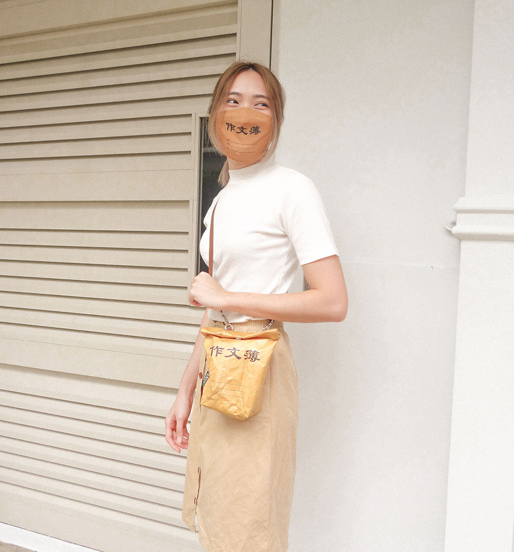 photo of a person wearing the wheniwasfour chinese composition book mask and kraft paper sling bag with a simple white top and a beige A line button down skirt