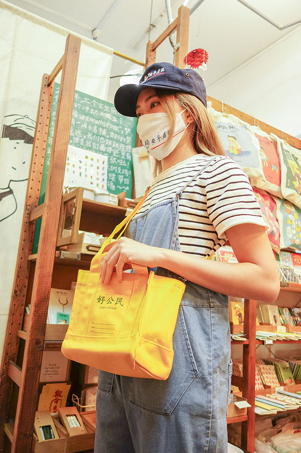 photo of a person wearing the wheniwasfour good morning towel mask and army cap with a navy blue and white striped short sleeved shirt and a loose denim jumpsuit trying on the yellow good citizen canvas sling bag in the wheniwasfour shop