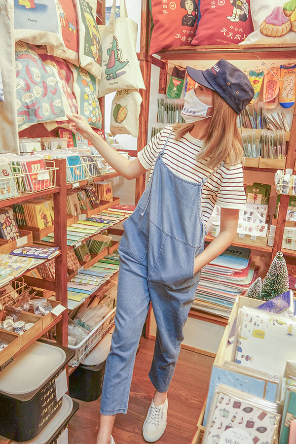 photo of a person wearing the wheniwasfour good morning towel mask and army cap with a navy blue and white striped short sleeved shirt and a loose denim jumpsuit with white sneakers browsing in the wheniwasfour shop