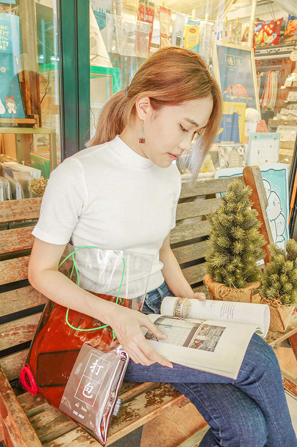 photo of a person wearing the wheniwasfour kopi and teh dabao bag dangling earrings with the kopi bag tote bag and pairing it with a simple white t-shirt and dark blue denim jeans while reading a book outside the wheniwasfour shop