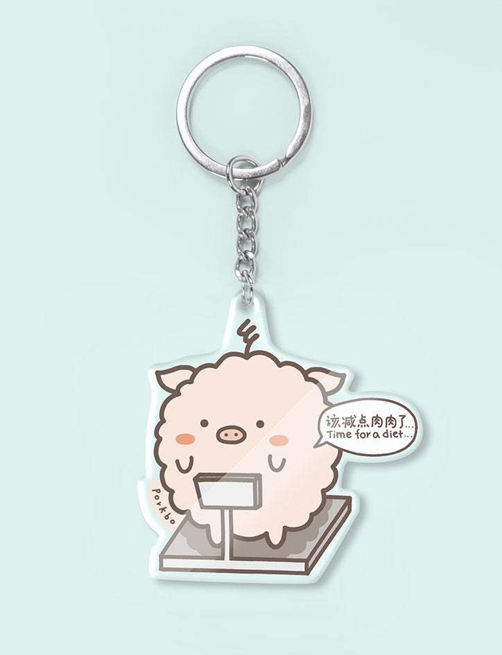 Cute pork fishball character on a weighing scale as a keychain